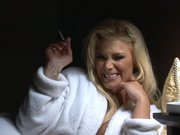 Shyla Stylez laying on the bed and smoking a cigarette